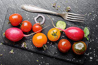 Top view at fresh organic vegetables on slate stone tray with spices aside closeup dark concept photo
