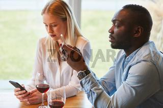 Multikulturelles Paar im Restaurant mit Smartphone