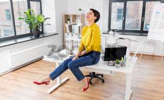 happy businesswoman sitting on desk at office