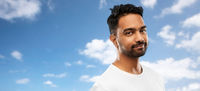 smiling young indian man over blue sky background