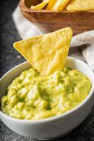 Corn nacho chips and avocado dip. Yellow tortilla chips and guacamole