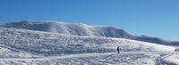 Skier downhill on ski slope at cold sun morning