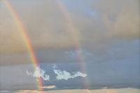 Doppelter Regenbogen vor Wolken am Himmel