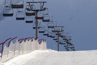 Snowy ski slope and chair-lift on high mountains at sunny winter evening