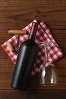 Vertical High angle view of a red wine bottle on a red and white checkered napkin