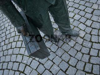 Mann im Anzug mit Aktenkoffer auf Steinpflaster