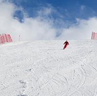 Skier descend on snowy ski slope at winter day