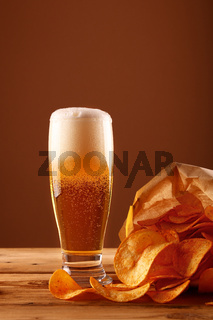 Close up beer glass and potato chips over brown