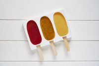 three different fruit smoothie popsicles in reusable silicone ice pop mold