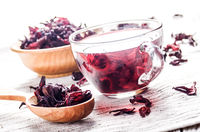 Closeup view at wooden bowl tea cup and spoon of dry hibiscus petals on linen cloth background