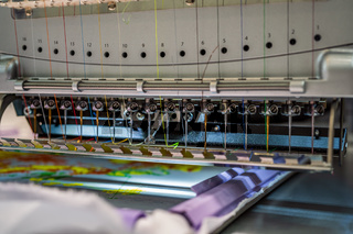 Automatic industrial sewing machine for stitch by digital pattern. Modern textile industry.