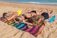 Three girls sunbathe together on beach at sea