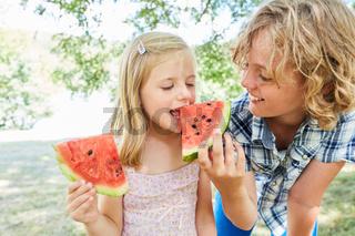 Junge gibt seiner Schwester ein Stück Melone