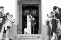 Newlyweds kissing while exiting the church after wedding ceremony, family and friends celebrating their love with the shower of soap bubbles, custom undermining traditional rice bath