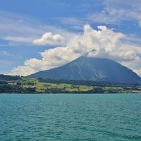 Turquoise Lake Thun. Mount Niesen surrounded by clouds. Bernese Oberland, Switzerland.