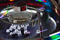 Black and white lottery balls in a rotating bingo machine. Number 12