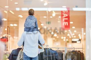 Mann und Kind vor einem Modegeschäft