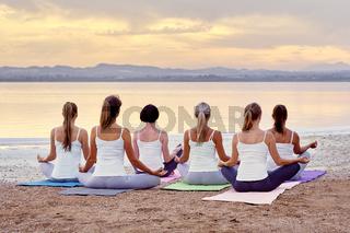 Back view women sitting in lotus pose meditating outdoors