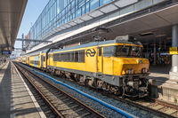 Railway station Utrecht with waiting train and travelers