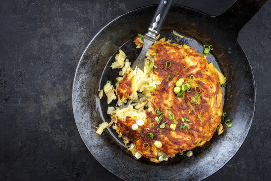 Traditional Swiss rosti as side dish with leek as top view in a frying pan with copy space left