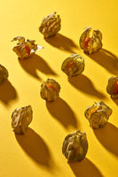 Top view close up of a pattern with yellow physalis fruit with shadows on a yellow background