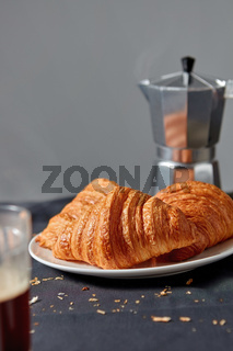 Coffee maker with homemade croissant on a gray background.