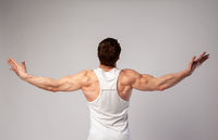 A man with a muscular body spread his arms to the side and looks up