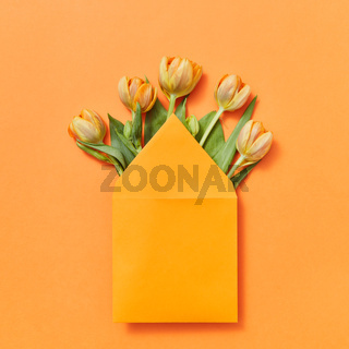 Mock up envelope with yellow tulips on an orange background.