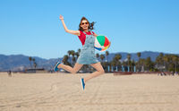 teenage girl in sunglasses jumping with beach ball