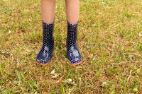 Child wearing rain boots on the grass