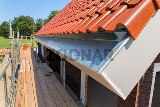 Zinc rain gutter with roof tiles and scaffolding
