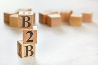 Three wooden cubes with letters B2B means Business to busines , on white table, more in background, space for text in right down corner