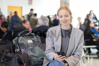 Cheerful female traveler smiling, looking at camera while reading on her cell phone while waiting to board a plane at departure gates at airport terminal.