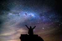 Silhouetted person hails the cosmos milky way starry night sky