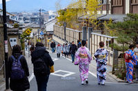 KYOTO, JAPAN - 08 FEB 2018: Two colorful young japanese girls dressed in traditional kimonos walking down a street in Gion