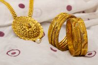 Close-up of artificial golden bangles and necklace.