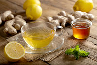 Energizing ginger tea with lemon hot served on a rustic wooden table