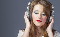 Teen redhead girl with helmet on her head listening to music on a flat gray background