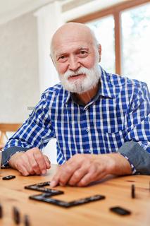 Alter Mann mit Demenz spielt Domino