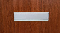 A mail slot on a wooden door