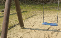 Children swing in closeup on a playground
