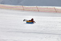 Young girl downhill on snow tube on ski resort at sun winter day