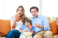 Family watching TV eating popcorn