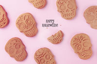 Happy Halloween greeting card with skull ginger cookies, shot from the top on a pink background