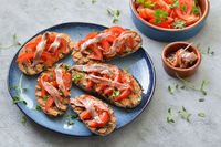 Grilled slices of bread with tomatoes an anchovy fillets
