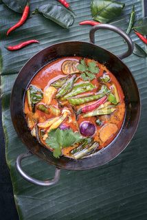 Traditional Thai kaeng phet red curry with vegetables as top view in a wok on a banana leaf