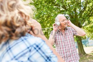 Großvater und Enkel mit Dosentelefon