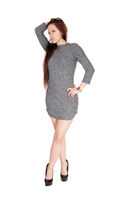 A slim pretty woman standing in a gray dress with legs crossed