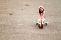 Little girl sits on the skate board