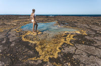 Woman stands by a small rock pool edged with yellow seaweed
